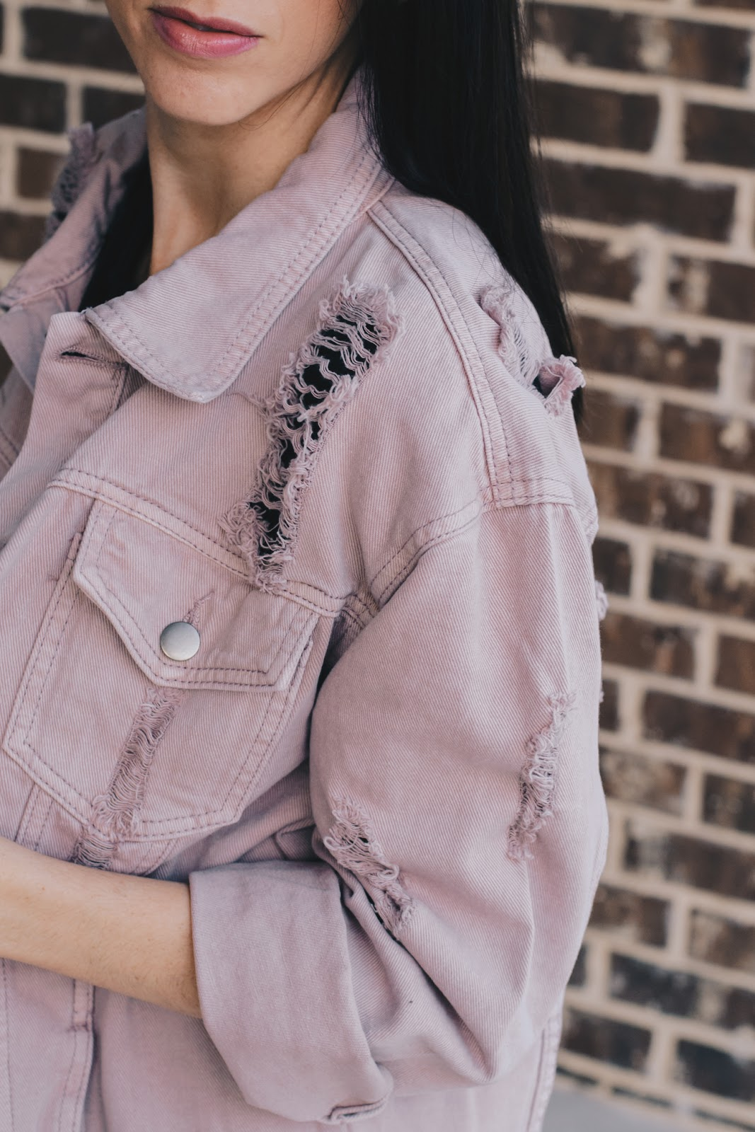 Detail of distressed denim jacket