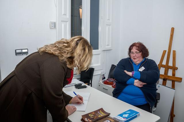La 2ª Tte. Alcalde Calpe Ana Sala Fernández firmando el libro de firmas de la exposición Fotografías de autor de J. Antonio Fontal