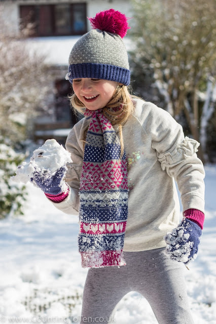 A young girl in jumper, scarf, hat and gloves looking at a large snowball in her hands and smiling