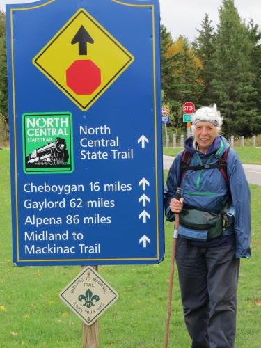 hiker at Midland to Mackinac Trail sign in Mackinaw City