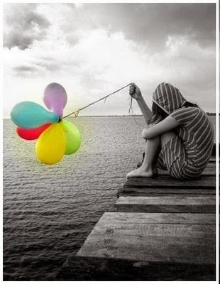 Joven sentada en muelle con la cabeza agachada entre las piernas y sosteniendo globos con mano derecha