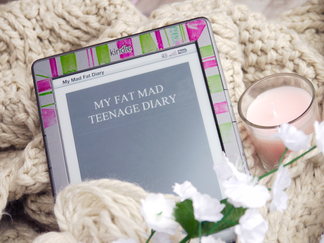 a kindle displaying my fat mad teenage diary propped up on a cream woollen scarf beside a pink candle
