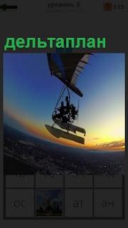 В воздузе в свете заката летит дельтаплан с пассажирами и пилотом, который управляет