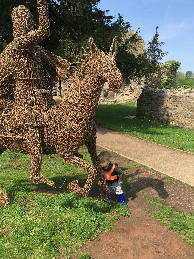 life size wicker horse and knight and toddler kissing horses leg