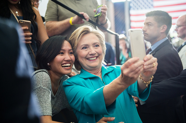 image of Hillary Clinton taking a selfie with an Asian American woman; they are both smiling broadly