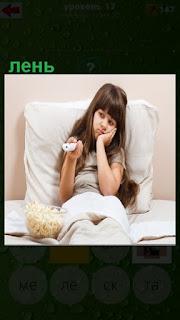 на постели лежит девочка которой лень вставать и она пользуется пультом для телевизора