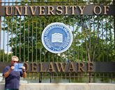 Joe holding the book in front of a gate that says University of Delaware