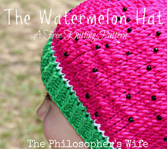 A girl is wearing a pink, green, and white hat with black beads.