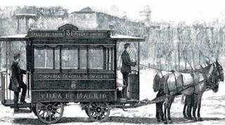 Dibujo de un carruaje, rippers, el conductor de pie al frente, y en la plataforma trasera el cobrador. En el lateral se llee: Villa de Madrid