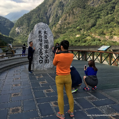 taking pictures beside the entrance stone at Taroko Gorge National Park in Hualien, Taiwan