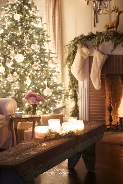 Christmas tree, fireplace, candles on bench in a living room