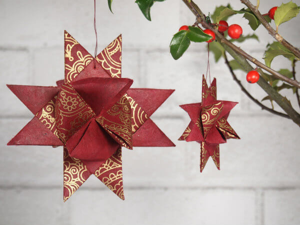 pair of red and gold henna design folded paper stars hanging on holly branch