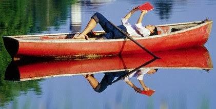 Funny woman reading in a boat joke story photo
