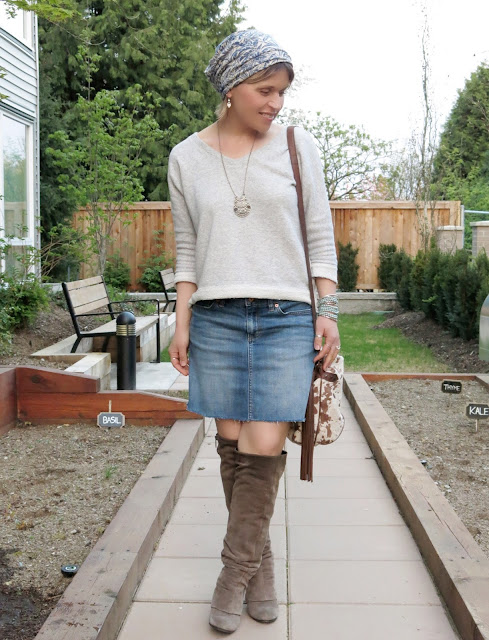 styling a raw-hemmed denim skirt with a sweatshirt, suede knee boots, and printed beanie