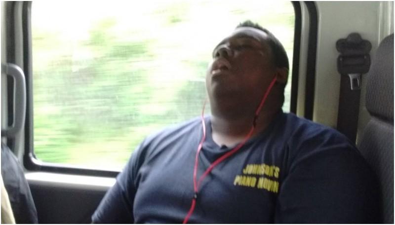 Seorang pria sedang mengorok di kereta api