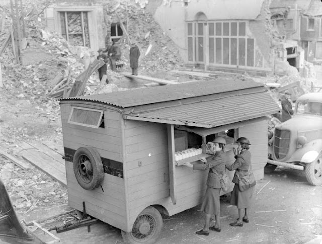 Women of the MTC - Miss Winifred Ashford and Mrs Pat Macleod open up their mobile canteen in front of a pile of rubble and some severely bomb-damaged houses, London, 1940.