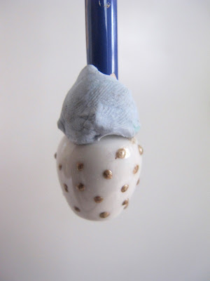 White dolls' house vase, with the end of a paintbrush blu tacked into it and painted with gold spots.