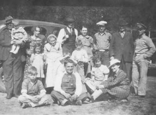 Group photo of family standing in front of old car during camp meeting from 1930's or 1940's