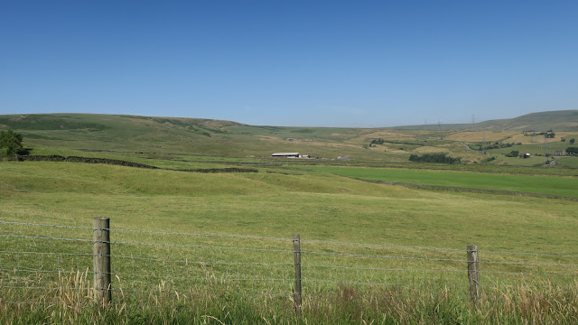 Farm buildings enfolded between moorland fields and fence.