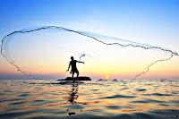 Bir balıkçı balık ağı atarken