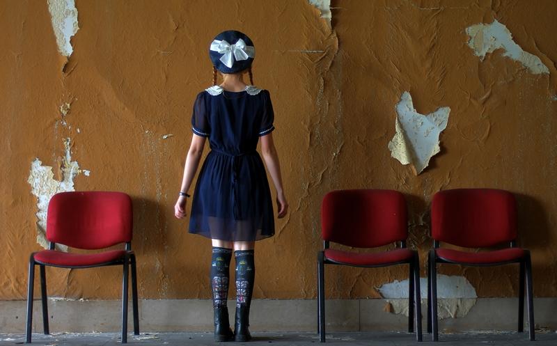 fille face à un mur de papier peint arraché dans un théatre abandonné de Belgique