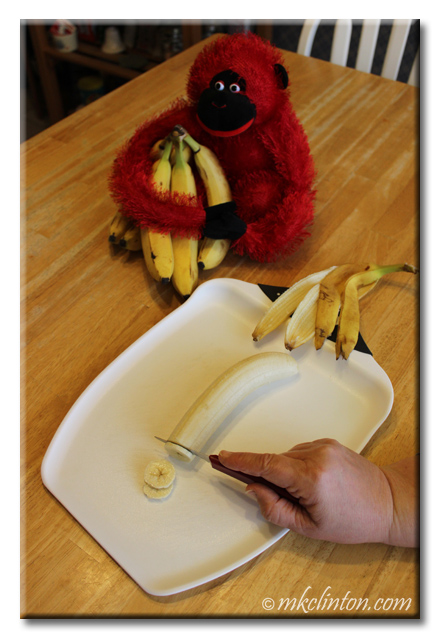 Banana being sliced on chopping board. Empty peel and red monkey holding bananas also on table