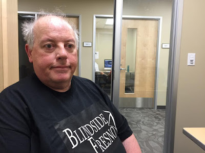 William Elliott, in Blindside Fresno T shirt, sits in editing suite, we can see through the glass wall to a corridor where there are several other editing rooms.