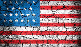 Image of an American flag on cracked pavement.