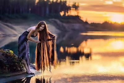 Она у озера на закате дня...