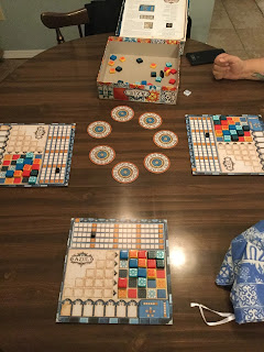 A completed game of Azul. Seven discs in a ring in the center of the table with three player mats around them, each with several tiles in the scored tiles section. The box top sits nearby, upside down, with several unused tiles in it, and the bag of available tiles rests close at hand.