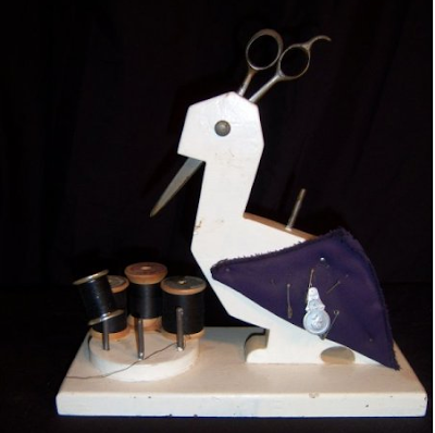 wooden bird holding scissors, with spools of thread on the base