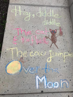 Chalked text of the Hey Diddle Diddle nursery rhyme with a chalked drawing of a cat