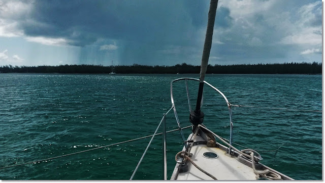 bow of sailboat with two anchor lines points towards rainstorm on the horizon.