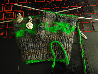 "A double-knit glove live on double-pointed needles  Yarn is brown, with a dragon motif around the cuff knit in green.  Two stitch markers with charms that read ""Faith"" are clipped into the work, and a stitch marker with a silver feather charm is at the side of the work."
