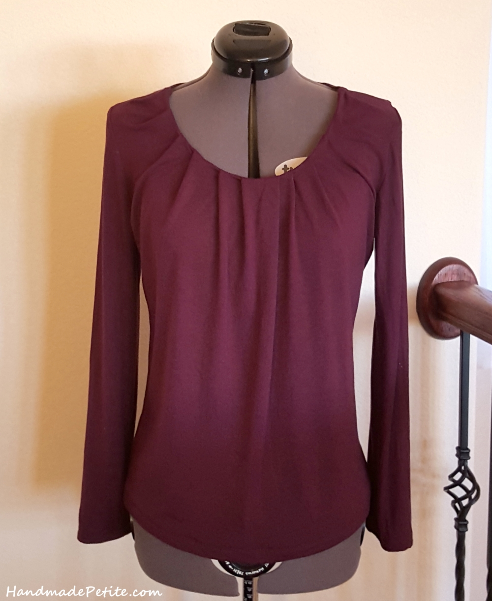 Sewing purple knit top with neck pleating detail.
