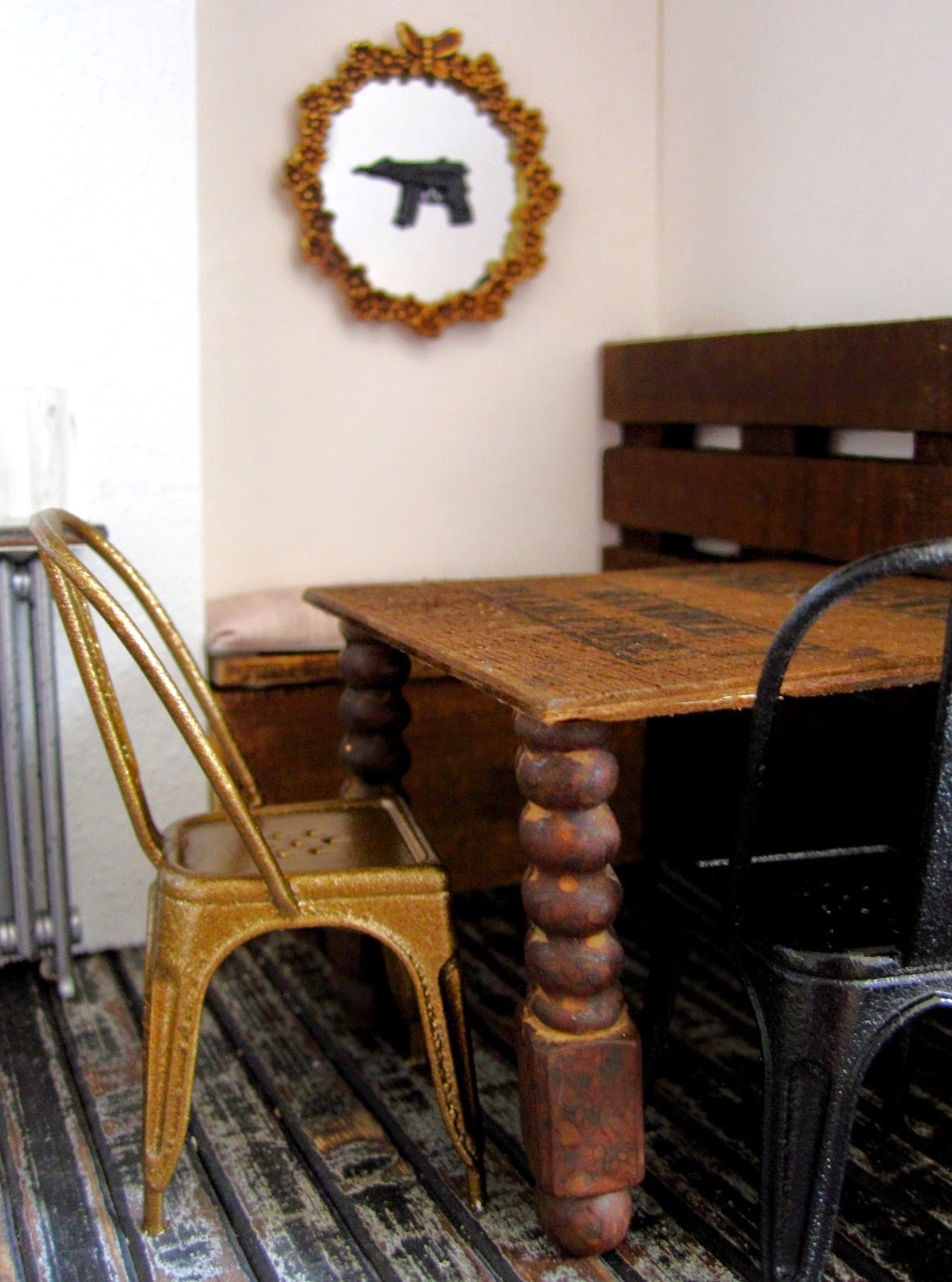 Modern dolls' house miniature cafe table and chairs On the wall is a mirror with a gun attached to it.
