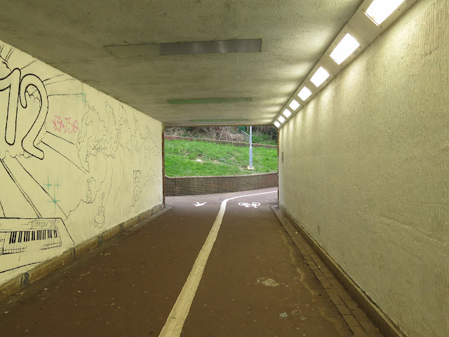 In the underpass. Murals on leaf, lights on right, grass glimpsed through opening beyond.