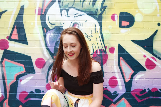 Lyd sits in front of bright cockatoo wall art wearing a black top and multicoloured trousers