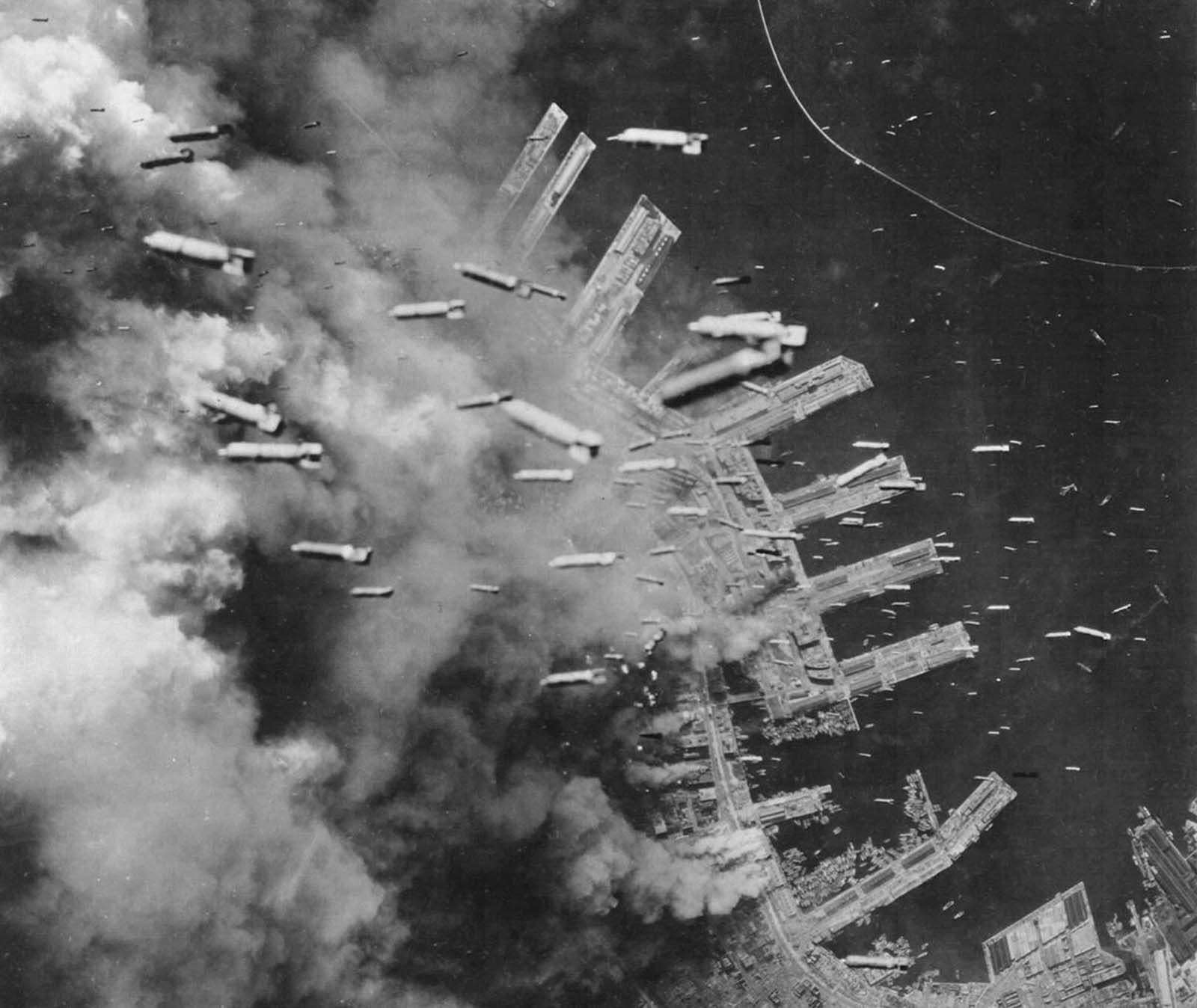 Incendiary bombs are dropped from B-29 Superfortresses of the U.S. Army Air Forces on already-burning landing piers and surrounding buildings in Kobe, Japan, on June 4, 1945.