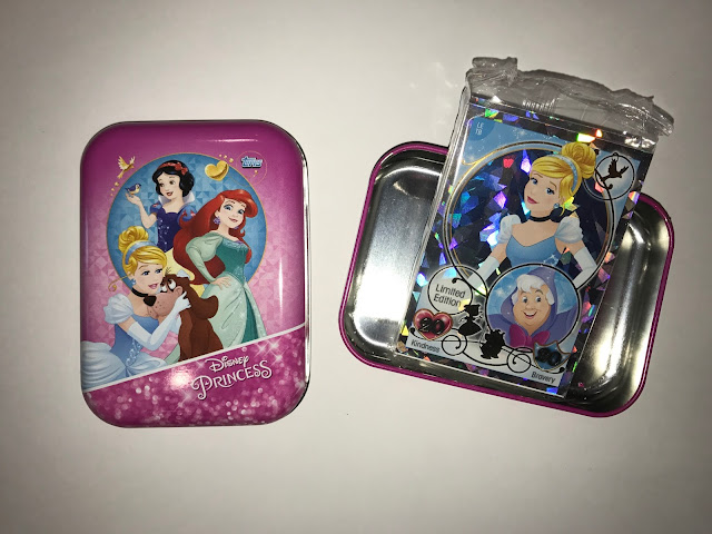 A small open tin with Cinderella, Arial and Snow White on the front with a pink background. In the other half of the tin is a packet of cards with a Cinderella Limited Edition card on show