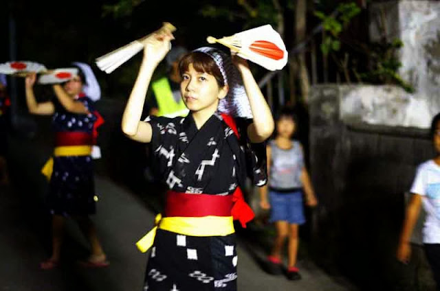 women do Eisa dance in streets at night