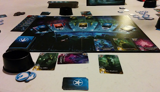 A game of Abyss in progress. The board is painted to resemble an arena, filled with aquatic creatures looking into the central area, as seen from the last row of one the sections of the audience. Across the top are six spaces for cards; the leftmost is occupied by a deck of cards, with single cards in the next three spaces. The five sections of the audience on the other side of the 'arena' each has a space for cards, labelled with an icon representing the five races of allies: jellyfish, crabs, seahorses, shellfish, and squids. Of these spaces, only the crabs and the seahorses do not have a stack of cards on them. Along the bottom of the board is a track of seven spaces for cards. The leftmost is occupied by a deck, and the three rightmost spaces each have a single face-up card illustrated with a lavish painting of a fish-man. Around the board are various items (cards, tokens, sea-shell-shaped cups to hold pearls, etc) belonging to the various players.