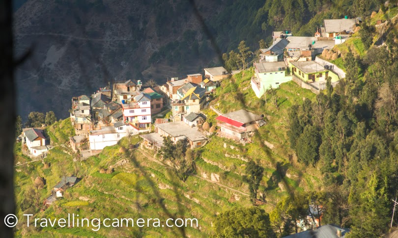 In the month of march, we visited this beautiful hill station in Himachal – Dalhousie. During the visit we stayed in Rashmi Villa which is clearly visible from surrounding hills of Dalhousie. When you are driving from Pathankot, you start seeing this place when you are 20 kilometers away from Dalhousie town. The huge flag installed in front of it an indicator. It's a beautifully located place around Dalhousie hills and near to famous Dalhousie Public School. This Photo Journey shares some of the views we experienced during our 3 days stay at Rashmi Villa.Here is the photograph of flag installed at Rashmi Villa. Dalhousie came in national news because of this flag. Dalhousie Public school also has a MIG-21 and soon they will be having a battle tank T-54.There is a nice ground around this flag and kids love playing around it. Rashmi Villa is a very old building in the campus of Dalhousie Public School and maintained by school authorities.It was continuously raining when we were in Dalhousie and we really enjoyed the hide-n-seek of clouds around us. Many times these clouds visited us at Rashmi Villa to welcome in Dalhousie.  Just on the left hand side, there are multiple layers of hills. These hills were having snow where we visited Dalhouise. More than snow, I really liked these beautiful houses having similar architecture and aligned symmetrically on this mountain. We were wondering about the people living on this hill. They must be getting far better views of surrounding and probably they would have an opportunity to look at other side of the hill from top. Khajjiar, Chamba and Bharmour are on the other side this hill. These portions are not visible from Rashmi Villa. Rashmi Villa is facing towards hills leading towards Pathankot and Ravi riverYou can see numerous villages on surrounding hills and I love these roofs of Himachali houses. Most of these houses have vibrant and multicolored shades in a unique way.Rashmi Villa is mainly surrounded by hills which have various sub-campuses of Dalhousie Public School. The MIG-21 is directly visible on the right side and river Ravi offers various shades during different time of the day. Dalhousie had got snowfall a week back, when we visited the town. There were some remains of the snow around Rashmi Villa as well. But most of the surrounding hills were white. Pir Pnajal mountain range in above photograph looks amazing. And the view of these hills from Gandhi Chowk is brilliant.The view of Ravi River from Rashmi Villa is my favorite. Every morning and evening I used to stand near the national flag to experience the colors of Ravi River. I wanted to see the river during sunset or sunrise, but hazy weather didn't allow me to even see the river during that time. I am sure that river must be looking stunning during clear days. Hope to be there soon and enjoy those brilliant landscapes again.