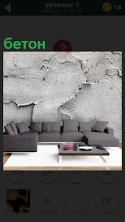 В комнате стоит диван, а на стене размазан бетон неряшливо