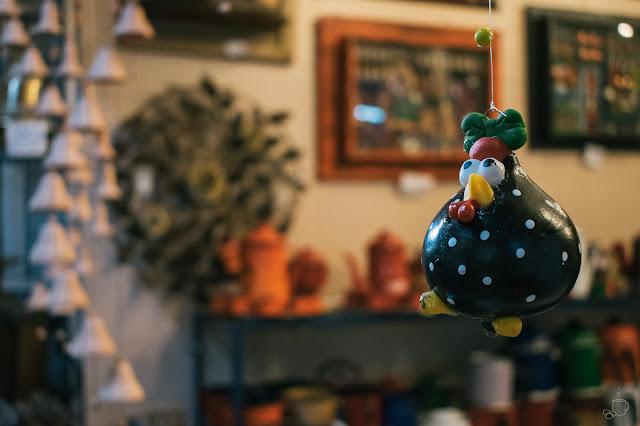 um móbile de galinha pendurado à frente de uma loja de artigos de decoração mineira dentro do mercado central