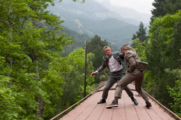 Daniel Craig as James Bond having a fistfight atop a train in Skyfall movieloversreviews.filminspector.com