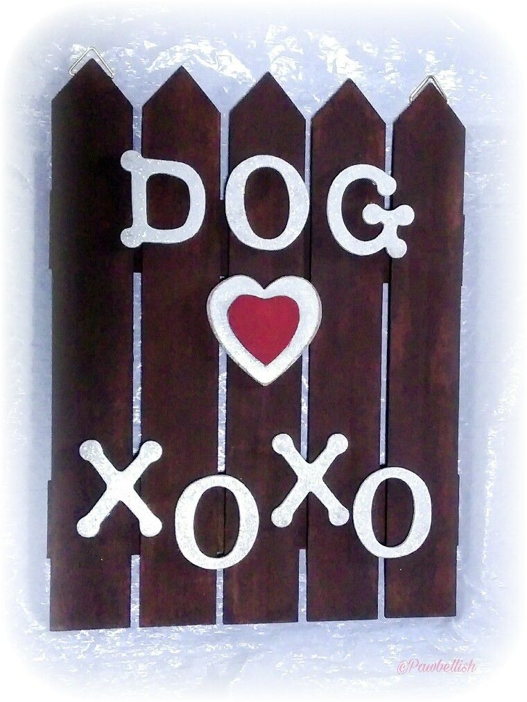 DIY painted wooden dog love sign displayed on a white wall