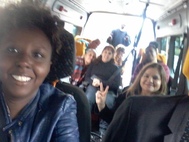 Grupo de passageiros dentro da van acessível, na foto temos seis passageiros sentados e o motorista em pé atrás de todos os passageiros.