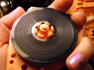 [Image: Close-up of the disc being held in the author's hand, removed from the box. The disc is small enough to fit on the palm.]