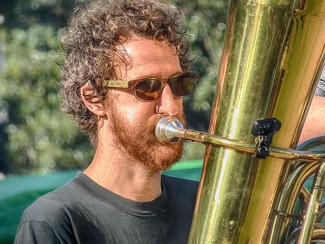 Retrato músico pelirrojo tocando la tuba.